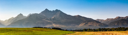 panorama of Tatra mountains in evening haze behind the forest and rural field