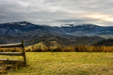 wooden fence on the meadow with green but frozen grass infront of high mountain range with snowy tops on a cloudy autumn day