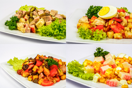 four salads with meat, tomatoes crab sticks, crackers, cucumbers, corn and egg on white plate for celebration table