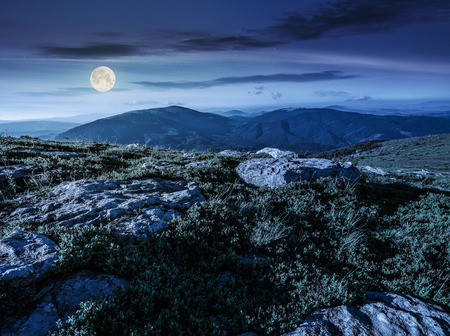 mountain summer landscape. meadow with huge stones among the grass on top of the hillside near the peak of mountain range at night in full moon light Stock Photo
