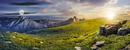 Summer landscape concept of Day and Night meet in High Tatra Mountains on a meadow with huge stones among the grass on top of the hillside near the peaks Stock Photo