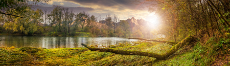 Composite landscape with river and falen tree on the shore in the forest in High Tatra Mountains in evening light