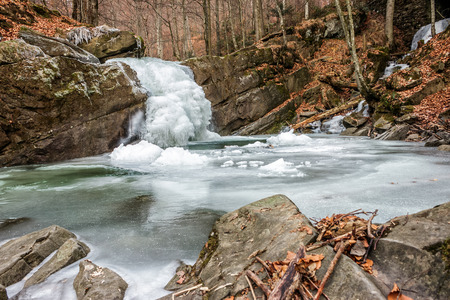 frozen waterfall on the  river among forest with old brown foliage on the ground Stock Photo