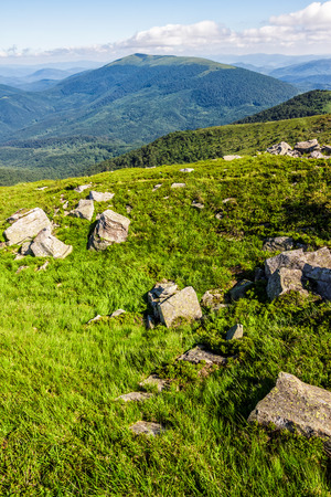 mountain summer landscape. meadow with huge stones among the grass on top of the hillside near the peak of mountain range
