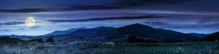 Summer landscape panoramic image of rural fields in mountains under cloudy sky at night in full moon light Stock Photo