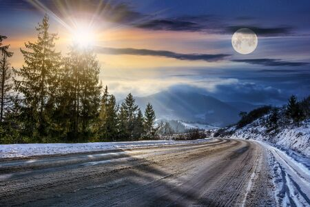 day and night concept of winter mountain landscape. road goes down to village throug spruce forest covered with snow on fresh frosty day