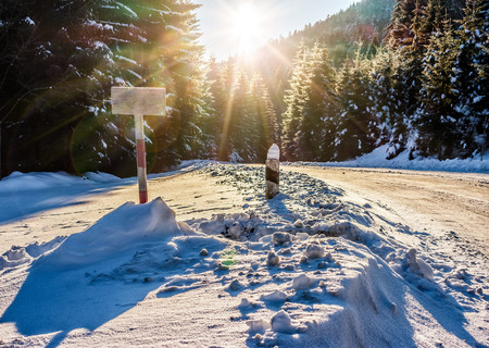 winter mountain landscape. wooden road sign on winding road that leads into the spruce forest covered with snow at sunrise Stock Photo