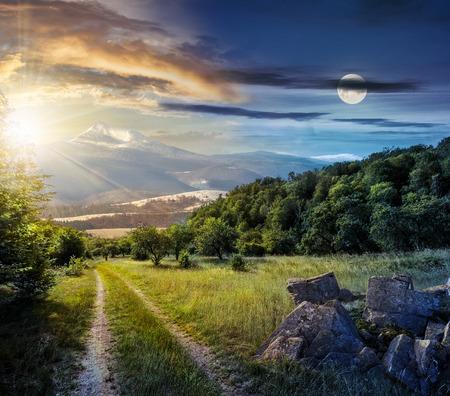 Concept dag en nacht tijd verandering. De winter komt samen met de lente samen. Vallei met bomen en keien op een gras. Weg door weide gaat naar bos in bergen met sneeuwpiek onder bewolkte lucht