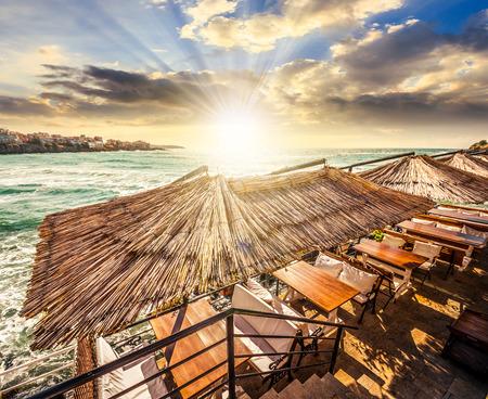 mesa de restaurante con banco y almohadas blancas en la orilla del mar en el casco antiguo en la luz del atardecer