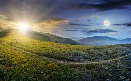day and night concept image with path through a large meadow on the hillside in high mountains
