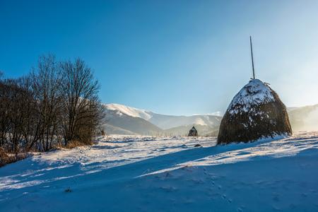 Stack of hay on a snowy hillside meadow in mountain area in winter
