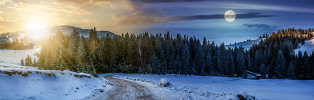 day and night time conept of panoramic mountain landscape in winter. winding road that leads into the spruce forest on a snowy meadow with sun and fool moon
