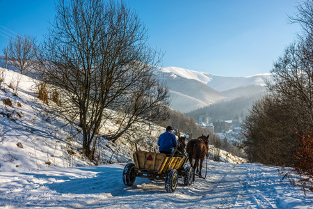man riding cart with twoo horses down the hill to village in snowy mountains Stock Photo
