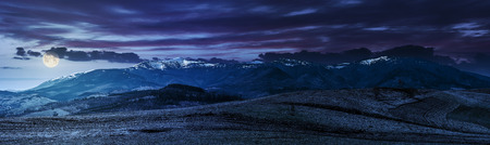 Early spring highland landscape. Panorama of rural fields on hill side in mountains with snowy peaks at night in full moon light