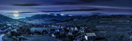 Early spring rural landscape. Panorama of village near the fields on hill side at the foot of the  mountains with snowy peaks at night in full moon light