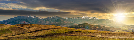 Early spring highland landscape. Panorama of rural fields on hill side in mountains with snowy peaks in evening light Stock Photo