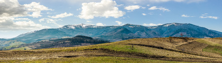 Early spring highland landscape. Panorama of rural fields on hill side in mountains with snowy peaks Stock Photo