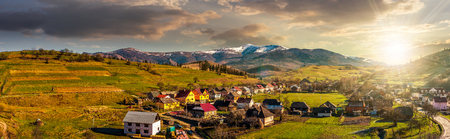 Early spring rural landscape. Panorama of village near the fields on hill side at the foot of the  mountains with snowy peaks in evening light