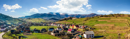 Early spring rural landscape. Panorama of village near the fields on hill side at the foot of the  mountains with snowy peaks