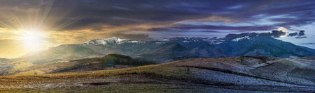 Day and night concept image of early spring highland landscape. Panorama of rural fields on hill side in mountains with snowy peaks with sun and moon