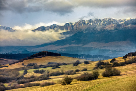 snowy peaks of Tatra mountains in evening haze behind the forest and rural field in autumn