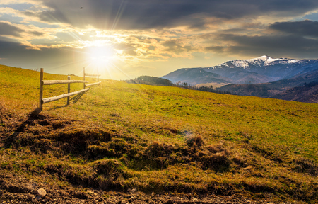 wooden fence on grassy hillside near mountains with snowy peaks in spring evening light Stock Photo