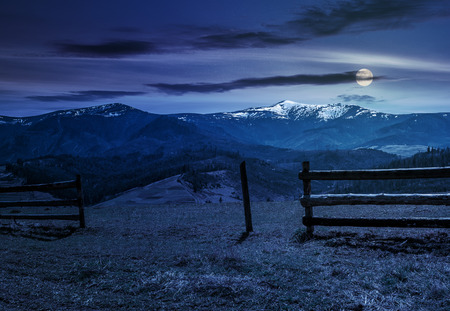 wooden fence on grassy hillside near mountains with snowy peaks in spring at night in full moon light