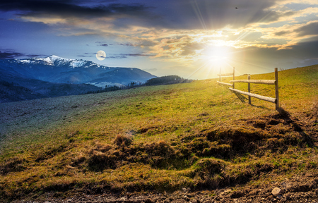 day and night transition time concept. wooden fence on grassy hillside near mountains with snowy peaks in spring