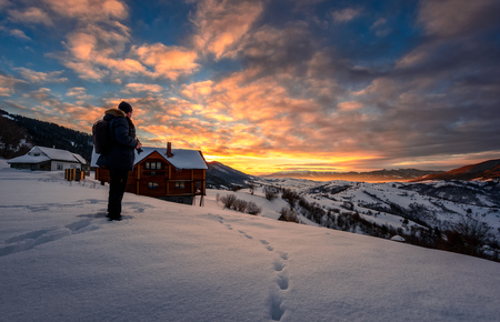 landscape photographer stands on the edge of hillside covered with snow near the village houses in mountainous rural area and looks on winter sunrise Stock Photo