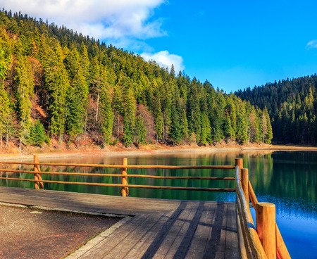 pier with fence on the Lake in mountain near coniferous forest in autumn sunset