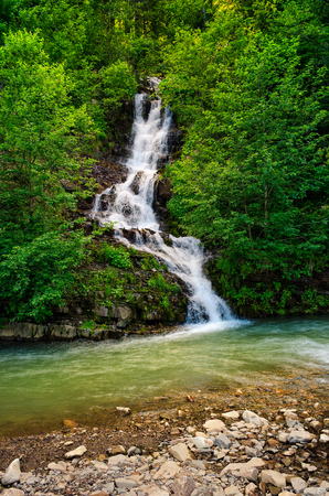 beautiful waterfall comes out of a hillside in forest and fall in to the mountain river