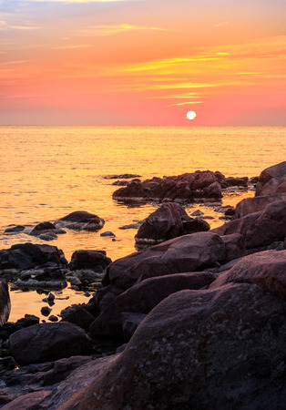 warm and calm sunrise over the rocky sea shore with huge boulders