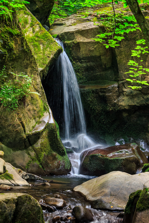 beautiful waterfall comes out of a huge stone in forest and fall in to the mountain river Stock Photo