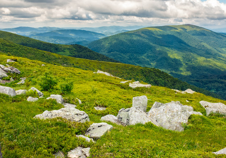 mountain summer landscape. meadow with huge boulders among the grass on top of the hillside near the peak of mountain ridge Stock Photo