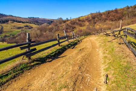 Spring time rural landscape. Wooden fence along the path through agricultural fields in Carpathian mountains Stock Photo