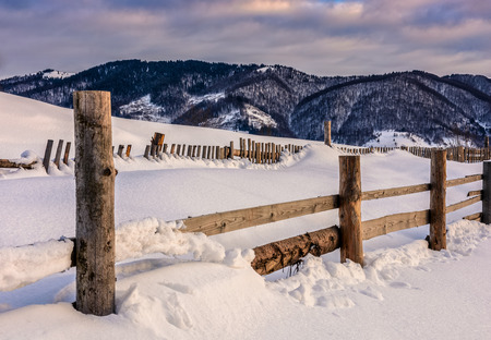 beautiful warm winter sunrise on cloudy morning in snow covered fields with wooden fence near rural area of Carpathian mountains
