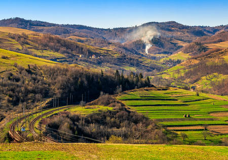 Spring time rural landscape. Railroad winds through agricultural fields in Carpathian mountains