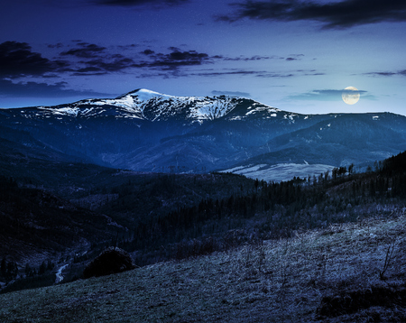 Stack of hay on hillside meadow  in mountain area in early spring at night in full moon light Stock Photo