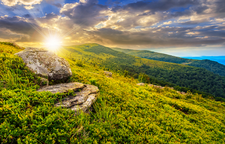 grassy meadow with giant boulders on the slope of a hill in Carpathian mountain ridge at dramatic sunset under cloudy sky. Beautiful summer landscape
