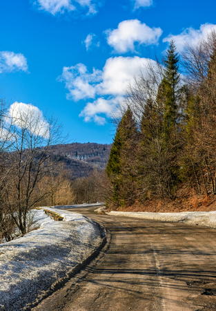 spring has come. last days of winter landscape. countryside curve road with snow on a side passes through forest in mountains Stock Photo