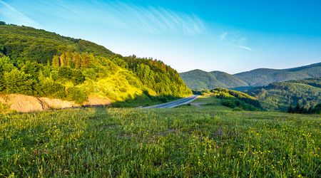 idyllic landscape in mountains at sunrise. vivid grassy field on a hill under the blue sky. road throug the mountain ridge with forests in morning light Stock Photo