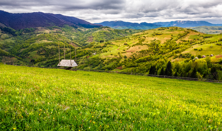 agricultural hay field in mountains. woodshed and fence on the grassy meadow. beautiful rural landscape