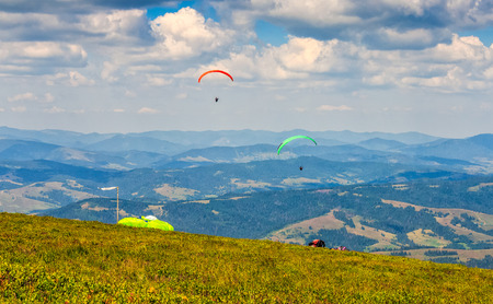 Skydivers fly over the mountains. Parachute extreme sport Stock Photo - 74352954