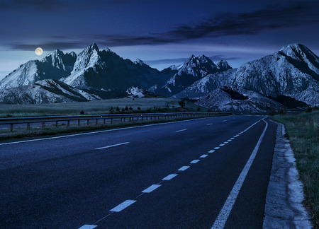Travel destination concept image. Composite landscape of High Tatra mountain ridge at night in full moon light. Straight asphalt highway through green hills leads to high peaks. Stock Photo