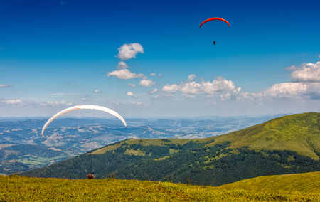 Skydivers fly over the mountains. Parachute extreme sport Stock Photo - 74353676