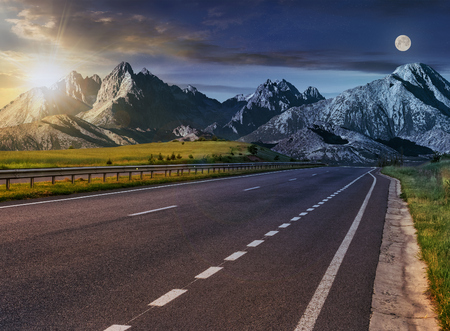 Day and nigght change Travel destination concept image. Composite landscape of High Tatra mountain ridge. Straight asphalt highway through green hills leads to high peaks. Stock Photo