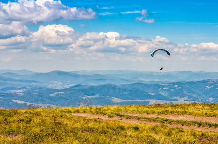 Skydivers fly over the mountains. Parachute extreme sport Stock Photo - 74355949