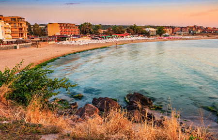 SOZOPOL, BULGARIA - SEPTEMBER 11, 2013: sunrise on sandy city beach in mellow season. Beautiful and warm weather on the shores of Black sea. Stock Photo