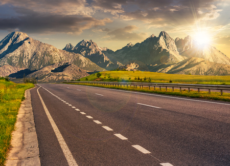 Travel destination concept image. Composite landscape of High Tatra mountain ridge at sunset. Straight asphalt highway through green hills leads to high peaks.
