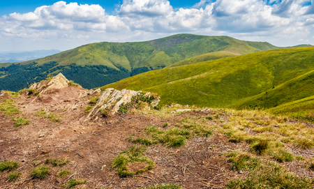 landscape with grassy meadow with giant boulders on the slope of a hill. Carpathian mountain ridge Borzhava on a beautiful sunny summer day
